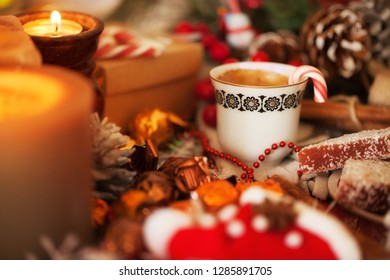 Cup of aromatic coffee with sweets and candles on warm relaxing background
