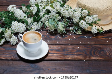 A cup of aromatic hot coffee, hat, beautiful twig of blooming White Spiraea (lat. Spiraea) isolated on dark vintage background. Concept of Spring. Space for Text. Selective focus.