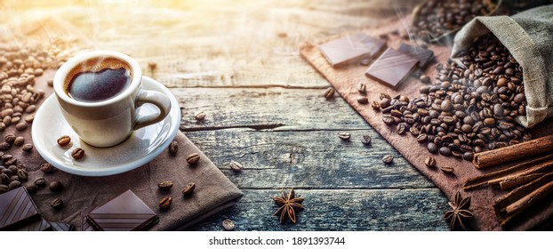 A cup of aromatic morning coffee, coffee beams, cinnamon, chocolate on the table. Nice background for coffee shop, restaurant menu.
