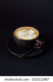 Cup of art latte on a cappuccino coffee isolated on black background