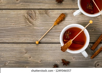 Cup of autumn winter hot spicy tea with cinnamon, anise and honey on a wooden background, top view. Selective focus.