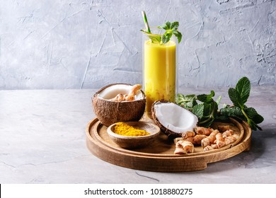 Cup of ayurvedic drink golden coconut milk turmeric iced latte with curcuma powder, crushed ice, mint and ingredients above on round wooden tray over grey kitchen table. Copy space