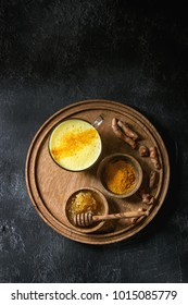 Cup of ayurvedic drink golden milk turmeric latte with curcuma powder on round wooden tray and ingredients above over black texture background. Top view, space