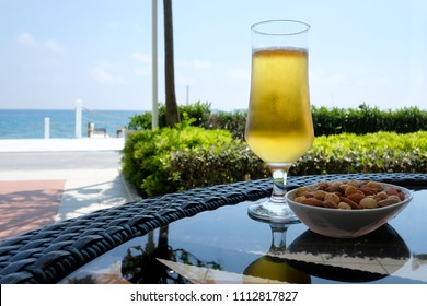 Cup of beer with nuts snacks on glass table. Sunny day near mediterranean sea. Summer time