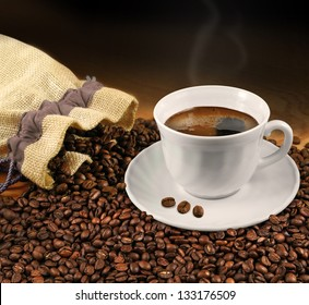 Cup of black coffee with bag and coffee beans