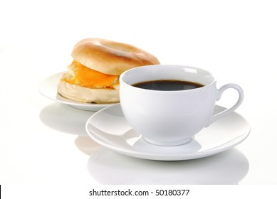A cup of black coffee and a bagel