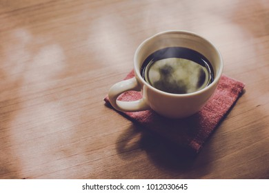 Cup of black coffee and coffee bean on wooden table with morning lighting top view and side view in coffee shop , by vintage retro hipster color tone , copy space