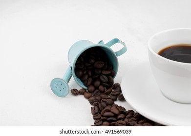 cup of black coffee with coffee beans and flower on white blackground