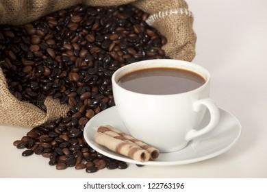 Cup of black coffee and beans isolated on white
