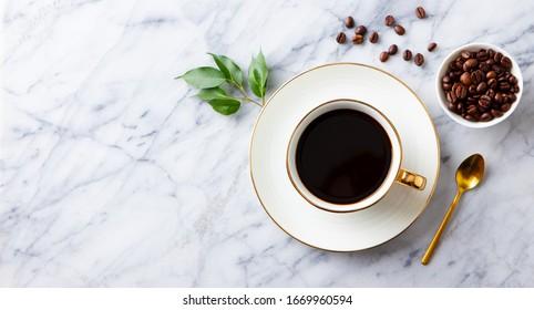 Cup of black coffee with coffee beans on marble table. Copy space. Top view.