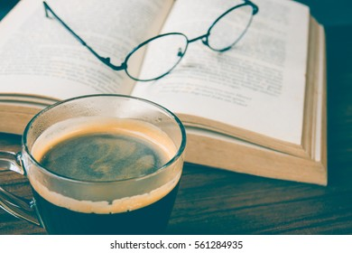 A cup of black coffee with book and glasses on table in coffee shop