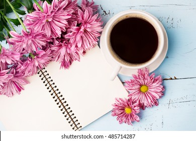 Cup of black coffee, Bouquet of flowers and Empty paper sheet on Rustic blue table from above, Beautiful vintage card, Top view, copy space for text, flat lay concept