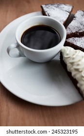 The cup of black coffee with chocolate cake viewed from above