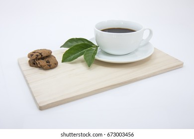 Cup of black coffee with chocolate cookies on wooden tray.