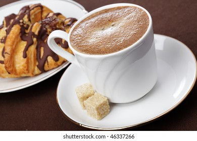 Cup of black coffee and chocolate croissant