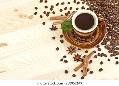 Cup of black coffee with cinnamon, green leaves, stars of anise and coffee beans on a wooden background