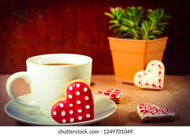 Cup of black coffee and cookies with icing suger  pieces on the dark table. Resting and enjoying time with coffee and sweets. Drink and snack concept