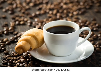 cup of black coffee, a croissant and coffee beans around