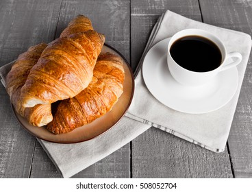 Cup of black coffee and croissant for breakfast on wooden background