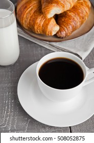 Cup of black coffee and croissant and milk  for breakfast on wooden background