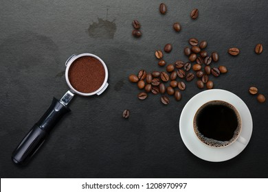 A cup of black coffee and filter holder of espresso with ground and scattered roasted coffee beans on dirty black table with coffee stains background, top view. Americano coffee and porta filter