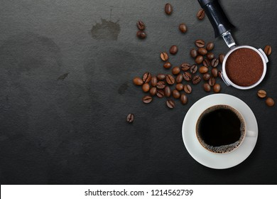 A cup of black coffee and filter holder of espresso with ground and scattered roasted coffee beans on dirty black table with coffee stains background, top view. Fresh coffee
