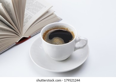 cup of black coffee with foam and open book