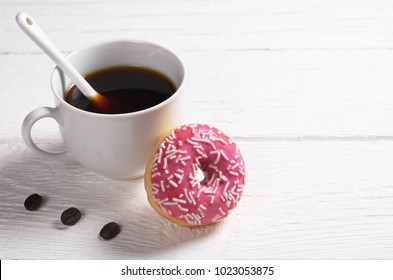 Cup of black coffee and glazed pink donut with sprinkles on white wooden table. Space for text
