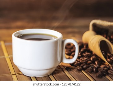 cup of black coffee and grains of coffee in a bag on a wooden table