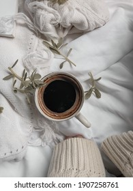 A cup of black coffee and green leaves scattered on white sheet. Aesthetic concept - Shutterstock ID 1907258761
