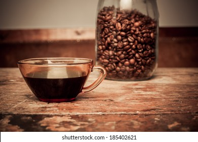 Cup of black coffee and jar of beans on a wooden table