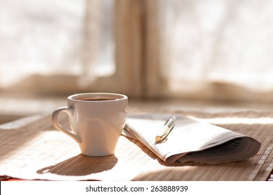 Cup of black coffee, newspaper and a pen against the window in the morning