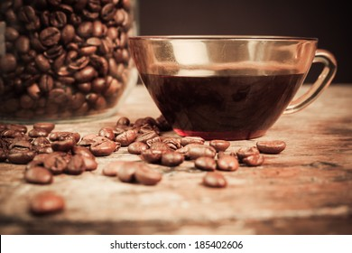 Cup of black coffee next to a jar filled with coffee beans