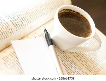 Cup of black coffee and old books