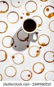 Cup of black coffee on a surface with many coffee stains.