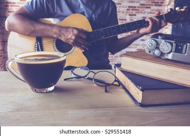Cup of black coffee on table with a man play guitar