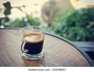 Cup of black coffee on a wooden table with copy space  - vintage effect style.