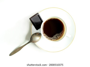 Cup of black coffee and a piece of black chocolate. Black aromatic coffee with foam in an elegant porcelain coffee cup and saucer, coffee spoon. White classic chinaware. Hot instant energetic drinks