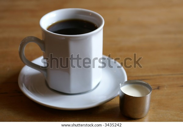 Cup of black coffee with a pot of cream on the side. Wooden tabletop.