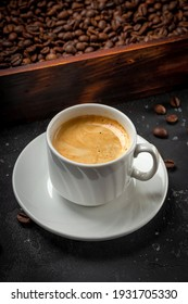 Cup of black coffee and roasted coffee beans in a wooden box vertical photo. High quality photo