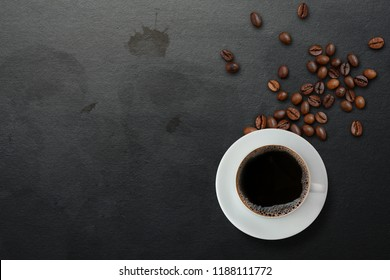 A cup of black coffee with scattered roasted coffee beans on dirty black table with coffee stains background, top view. Americano coffee