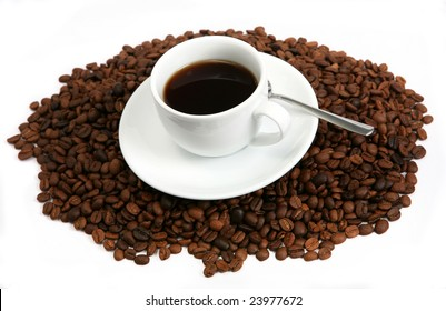 A cup with black coffee sitting on a pile of beans, horizontal,