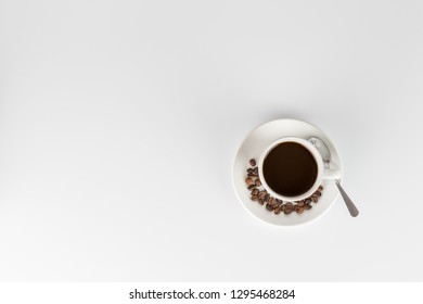 Cup of black coffee with some beans on the saucer, on a white background
