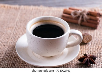 Cup of black coffee in cup, star anise, cinnamon sticks on wooden table