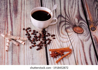 A cup of black coffee, wafer rolls with chocolate, cinnamon sticks and anise on a wooden table. View from above.
