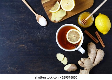 Cup of black natural tea with ginger, lemon and honey on wooden rustic background. Healthy drink. Hot winter beverage concept.