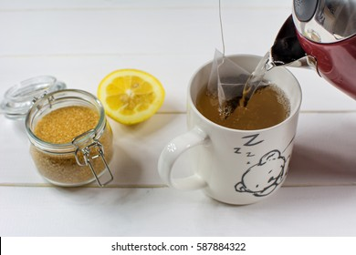 Cup of black tea and brown sugar inside glass jar on wooden background.