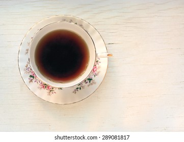 Cup of black tea in a china cup and saucer, on a distressed white table top.