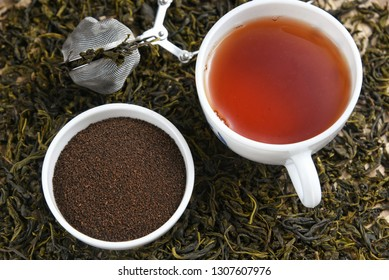 Cup of black tea and heap of dried organic tea leaves, dust and infuser  Munnar, Kerala, India. Aromatic herbal Indian beverage for relaxation, stress relief. healthy drink has antioxidants, nutrients