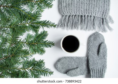 Cup of black tea, knitted mittens and scarf, decorated with pine branches on white table. Cozy minimalist winter forest composition. Top view, flat lay